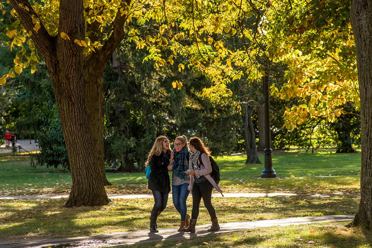 Three girls walking and laughing on the oval in autumn